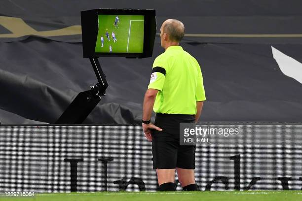 Referee Mike Dean checks the VAR pitch side screen before disallowing a goal from Manchester City during the English Premier League football match...