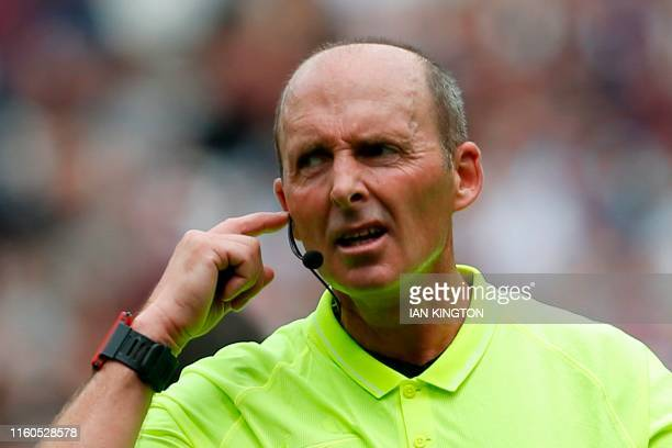 Referee Mike Dean communicates with the VAR as a Manchester City penalty which was saved is being checked and ruled that it must be retaken during...