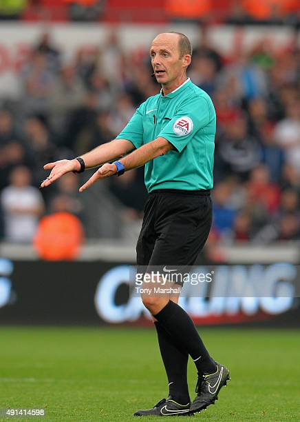 Referee Mike Dean during the Barclays Premier League match between Swansea City and Tottenham Hotpsur at the Liberty Stadium on October 4 2015 in...