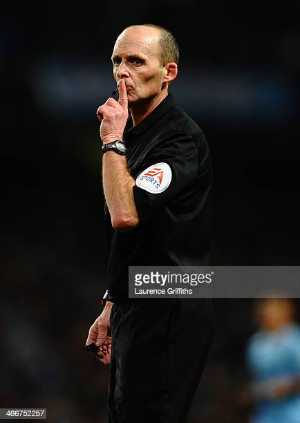 Referee Mike Dean gestures during the Barclays Premier League match between Manchester City and Chelsea at Etihad Stadium on February 3 2014 in...