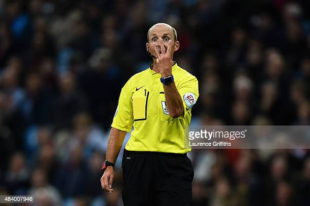 Referee Mike Dean gestures during the Barclays Premier League match between Aston Villa and Manchester United on August 14 2015 in Birmingham United...