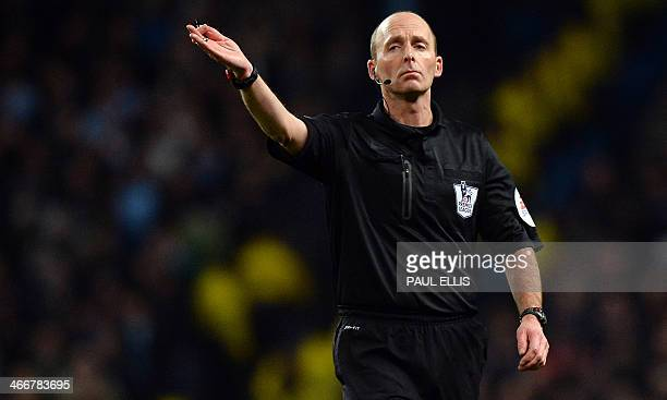 Referee Mike Dean gestures during the English Premier League football match between Manchester City and Chelsea at The Etihad Stadium in Manchester...