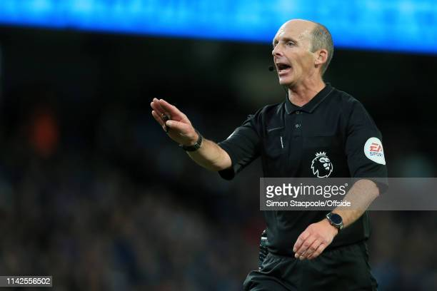 Referee Mike Dean gestures during the Premier League match between Manchester City and Leicester City at the Etihad Stadium on May 6 2019 in...