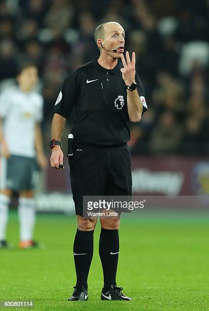 Referee Mike Dean gestures during the Premier League match between West Ham United and Manchester United at London Stadium on January 2 2017 in...