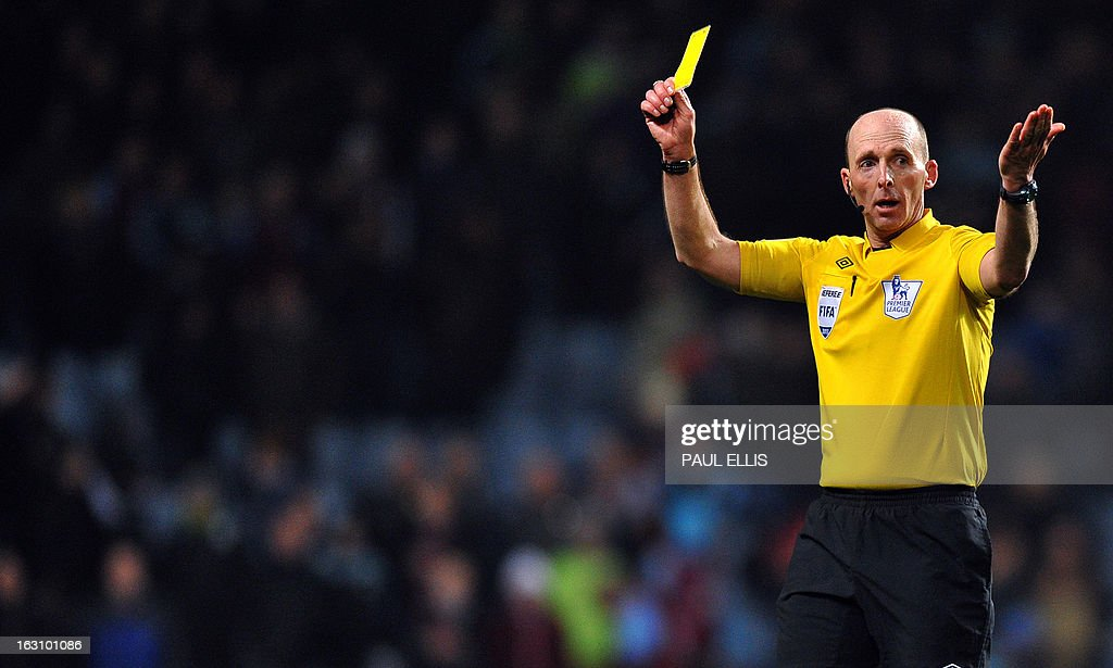 Referee Mike Dean gives a yellow card for Aston Villa's English midfielder Fabian Delph after a hand ball during the English Premier League football match between Aston Villa and Manchester City at Villa Park in Birmingham, central England, on March 4, 2013. Manchester City won the match 1-0. AFP PHOTO/Paul Ellis