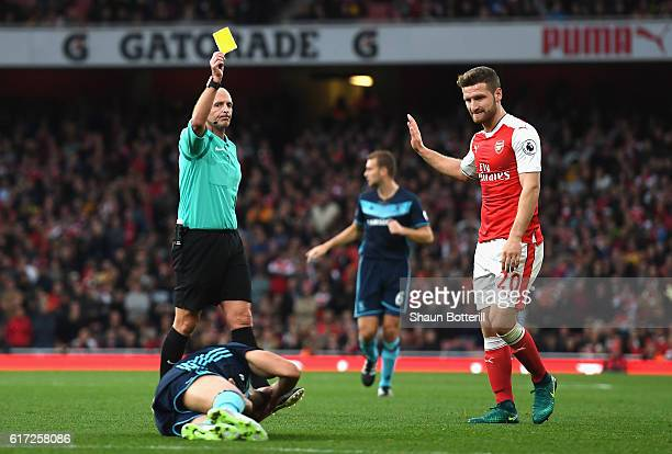 Referee Mike Dean gives Shkodran Mustafi of Arsenal a yellow card during the Premier League match between Arsenal and Middlesbrough at the Emirates...