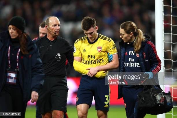 Referee Mike Dean helps Kieran Tierney of Arsenal leave the pitch following an injury during the Premier League match between West Ham United and...