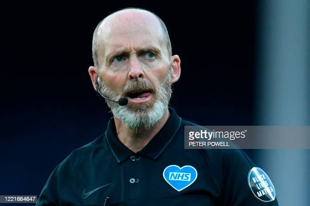 Referee Mike Dean is seen seen with an NHS and a Black Lives Matter patch on his jersey as he officiates during the English Premier League football...