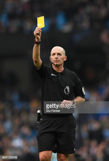 Referee Mike Dean issues a yellow card during the Premier League match between Manchester City and Swansea City at Etihad Stadium on February 5 2017...