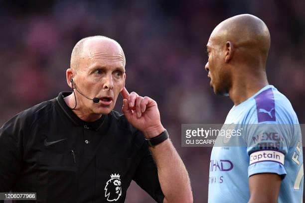 Referee Mike Dean listens to Manchester City's Brazilian midfielder Fernandinho during the English Premier League football match between Manchester...