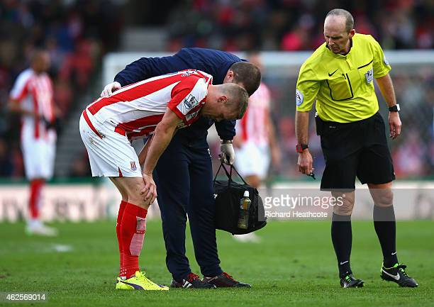 Referee Mike Dean looks on as Ryan Shawcross of Stoke City receives treatment during the Barclays Premier League match between Stoke City and Queens...