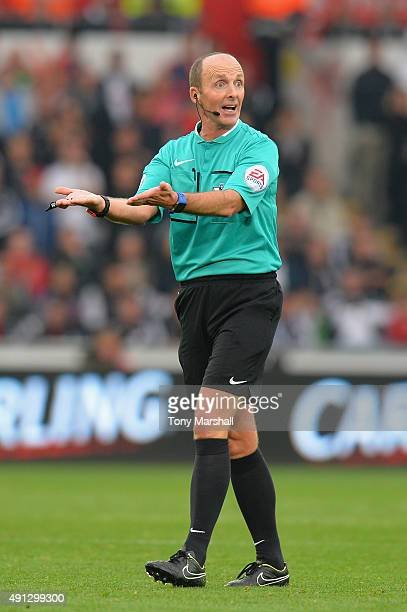 Referee Mike Dean makes a point during the Barclays Premier League match between Swansea City and Tottenham Hotspur at Liberty Stadium on October 4...