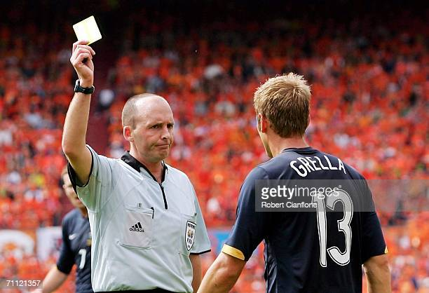 Referee Mike Dean of England show Vince Grella the yelow card during the international friendly match between Netherlands and Australia at De Kuip...