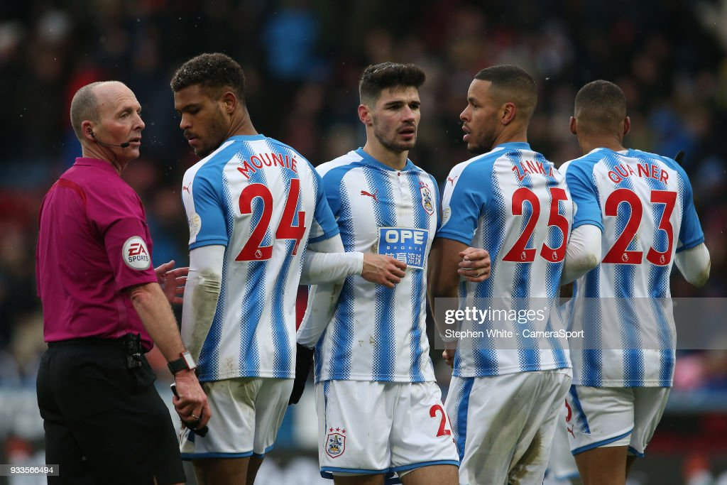 Referee Mike Dean positions Huddersfield Town's Steve Mounie, Christopher Schindler, Mathias Zanka Jorgensen and Collin Quaner the correct distance away from the ball for a free kick during the Premier League match between Huddersfield Town and Crystal Palace at John Smith's Stadium on March 17, 2018 in Huddersfield, England.