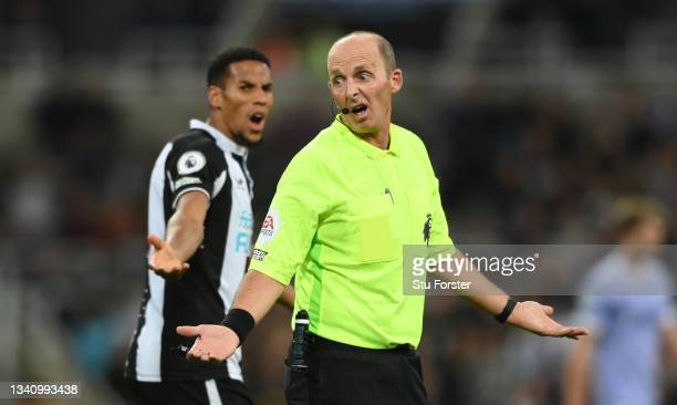Referee Mike Dean reacts as Isaac Hayden looks on during the Premier League match between Newcastle United and Leeds United at St. James Park on...