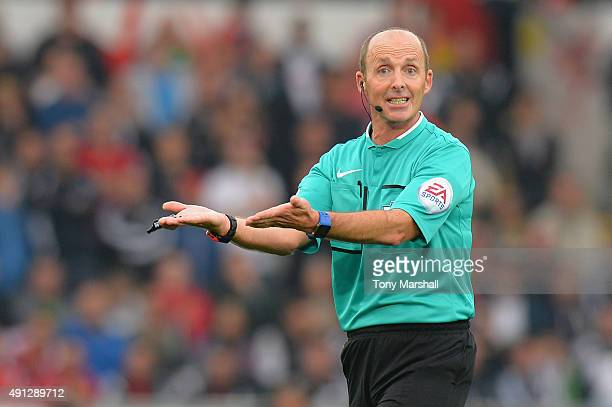 Referee Mike Dean reacts during the Barclays Premier League match between Swansea City and Tottenham Hotspur at Liberty Stadium on October 4 2015 in...