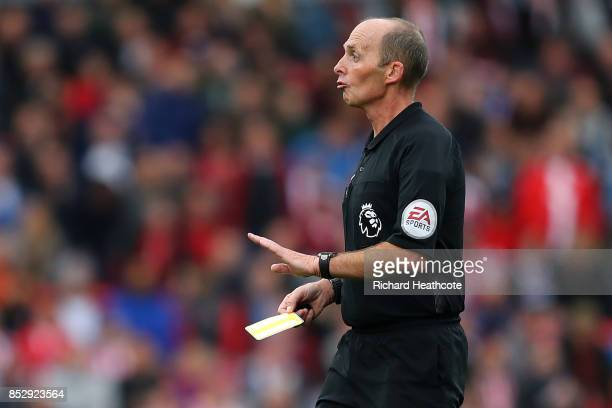 Referee Mike Dean shows a yellow card during the Premier League match between Stoke City and Chelsea at Bet365 Stadium on September 23 2017 in Stoke...