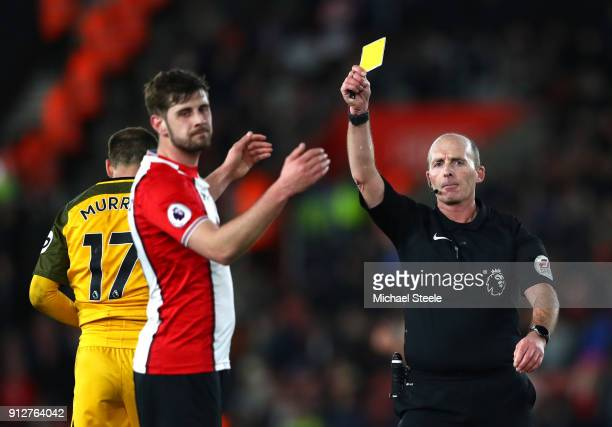Referee Mike Dean shows a yellow card to Jack Stephens of Southampton during the Premier League match between Southampton and Brighton and Hove...