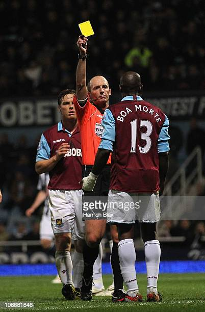 Referee Mike Dean shows a yellow card to Luis Boa Morte of West Ham leading to a goal from a penalty to West Bromwich during the Barclays Premier...