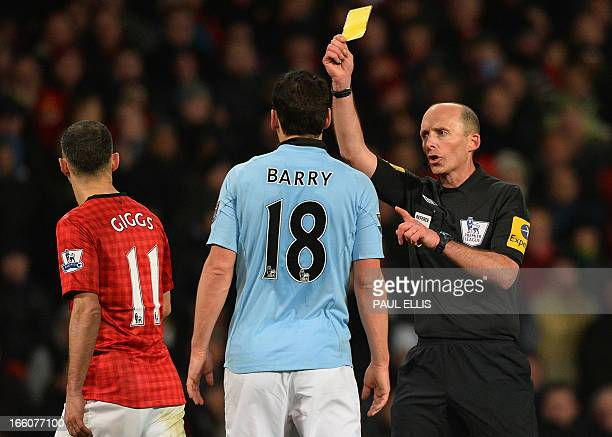 Referee Mike Dean shows a yellow card to Manchester City's English midfielder Gareth Barry during the English Premier League football match between...