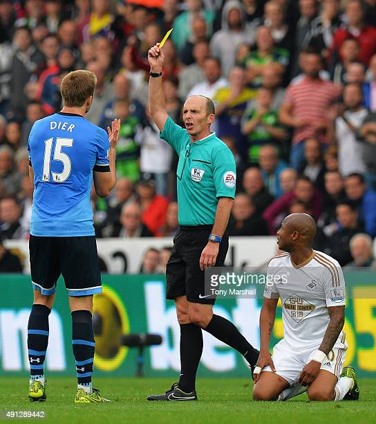 Referee Mike Dean shows Eric Dier of Tottenham Hotspur a yellow card during the Barclays Premier League match between Swansea City and Tottenham...
