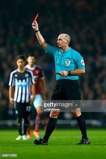 Referee Mike Dean shows Moussa Sissoko of Newcastle United a red card during the Barclays Premier League match between West Ham United and Newcastle...