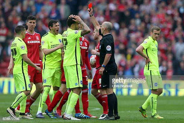 Referee Mike Dean shows the red card to Dale Stephens of Brighton and Hove Albion during the Sky Bet Championship match between Middlesbrough and...