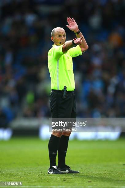Referee Mike Dean signals during the Premier League match between Brighton Hove Albion and Newcastle United at American Express Community Stadium on...
