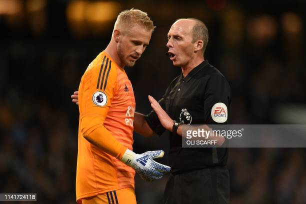 Referee Mike Dean talks with Leicester City's Danish goalkeeper Kasper Schmeichel during the English Premier League football match between Manchester...
