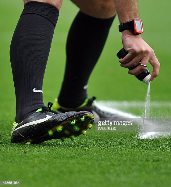 Referee Mike Dean uses vanishing spray to mark the pitch for a free kick during the English Premier League football match between Manchester United...