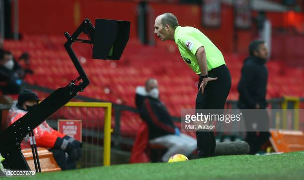 Referee Mike Dean views the VAR monitor during the Premier League match between Manchester United and Southampton at Old Trafford on February 02,...