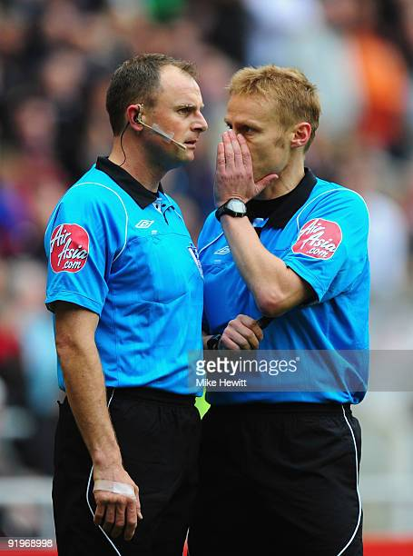 Referee Mike Jones discusses the Sunderland goal with his assistant Andy Newbold during the Barclays Premier League match between Sunderland and...