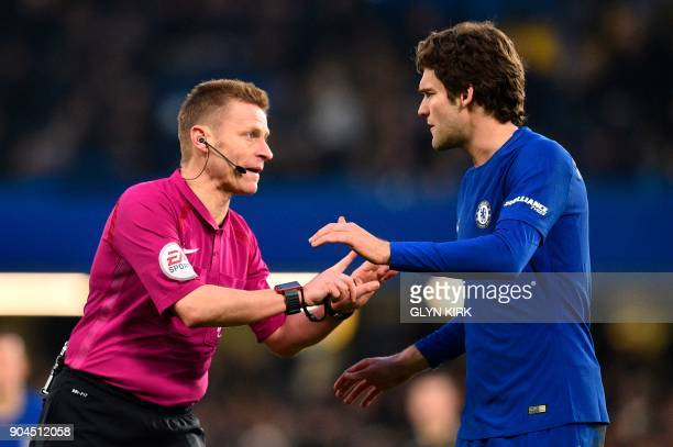 Referee Mike Jones has words with Chelsea's Spanish defender Marcos Alonso during the English Premier League football match between Chelsea and...