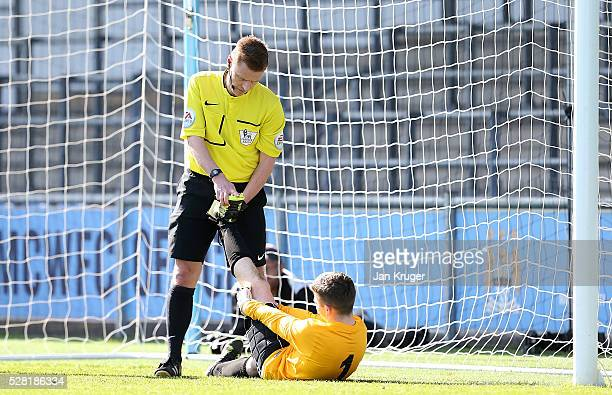 Referee Mike Jones helps Jake Dean Goalkeeper of Blacon High School with cramps during the under 16 Schools' Cup final match between Thomas Telford...