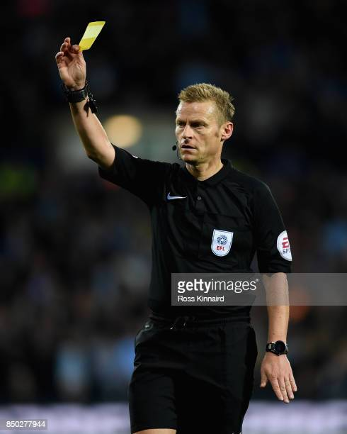 Referee Mike Jones holds up a yellow card during the Carabao Cup Third Round match between West Bromwich Albion and Manchester City at The Hawthorns...