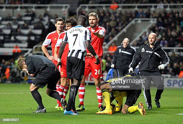 Referee Mike Jones is accidentally felled by an arm from Newcastle's Moussa Sissoko during the Barclays Premier League match between Newcastle United...
