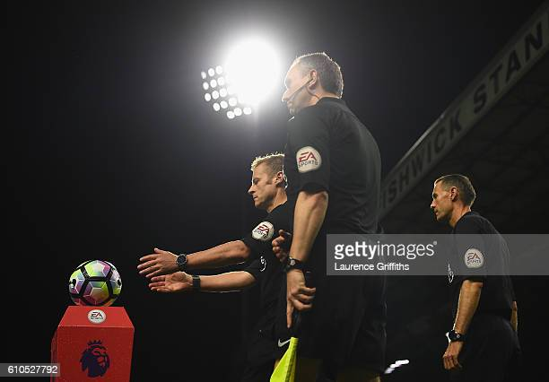 Referee Mike Jones leads the players onto the pitch during the Premier League match between Burnley and Watford at Turf Moor on September 26 2016 in...