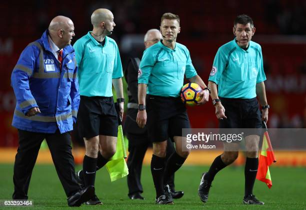 Referee Mike Jones leaves the field with assistants after the Premier League match between Manchester United and Hull City at Old Trafford on...