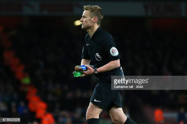 Referee Mike Jones picks up some bottles which have been thrown onto the pitch during the Premier League match between Arsenal and Leicester City at...