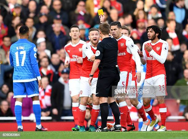 Referee Mike Jones shows Shkodran Mustafi of Arsenal a yellow card during the Premier League match between Arsenal and AFC Bournemouth at Emirates...
