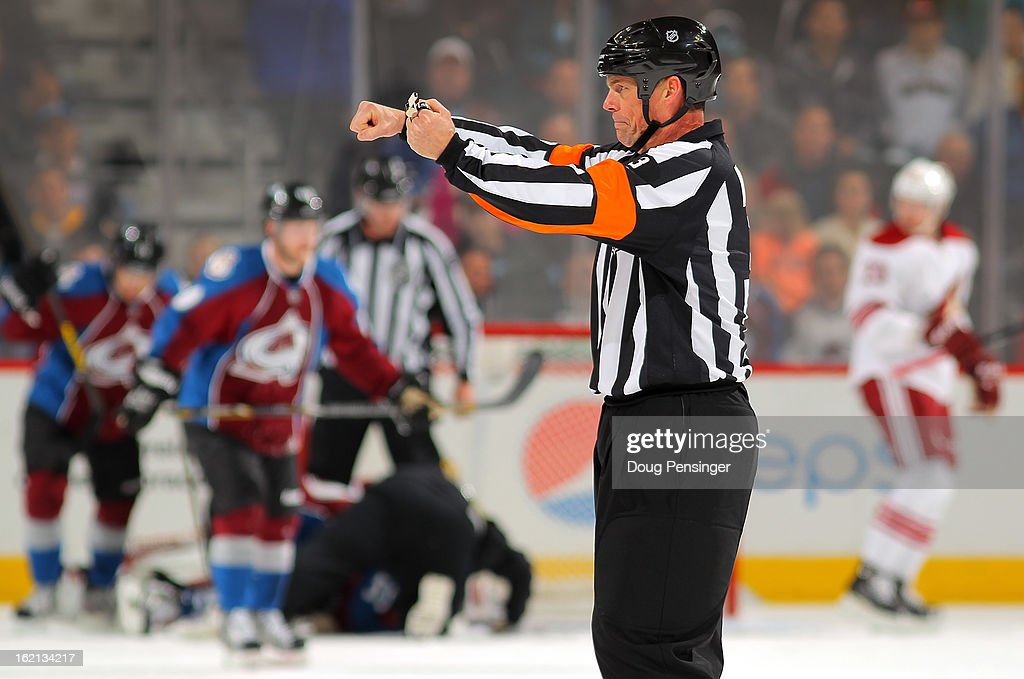 Referee Mike Leggo #3 calls a penalty as the Phoenix Coyotes face the Colorado Avalanche at the Pepsi Center on February 11, 2013 in Denver, Colorado. The Coyotes defeated the Avalanche 3-2 in overtime.