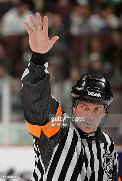 Referee Mike Leggo raises his hand during the game between the Dallas Stars and the Vancouver Canucks at General Motors Place on March 11, 2006 in...