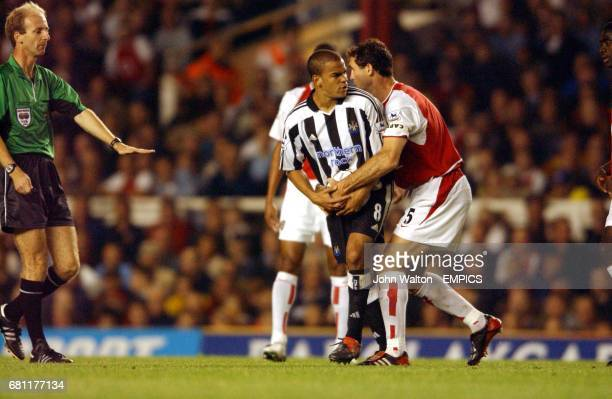 Referee Mike Riley calls for calm as Arsenal's captain Martin Keown tries to grab the ball off Newcastle United's Kieron Dyer
