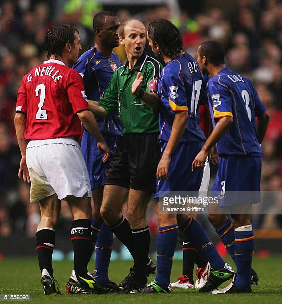Referee Mike Riley tries to keep the peace between Gary Neville of Man Utd and Edu of Arsenal during the FA Barclays Premiership match between...