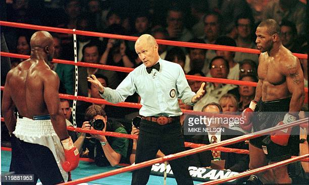 Referee Mills Lane steps between World Boxing Association heavyweight champion Evander Holyfield and challenger Mike Tyson during the third round of...
