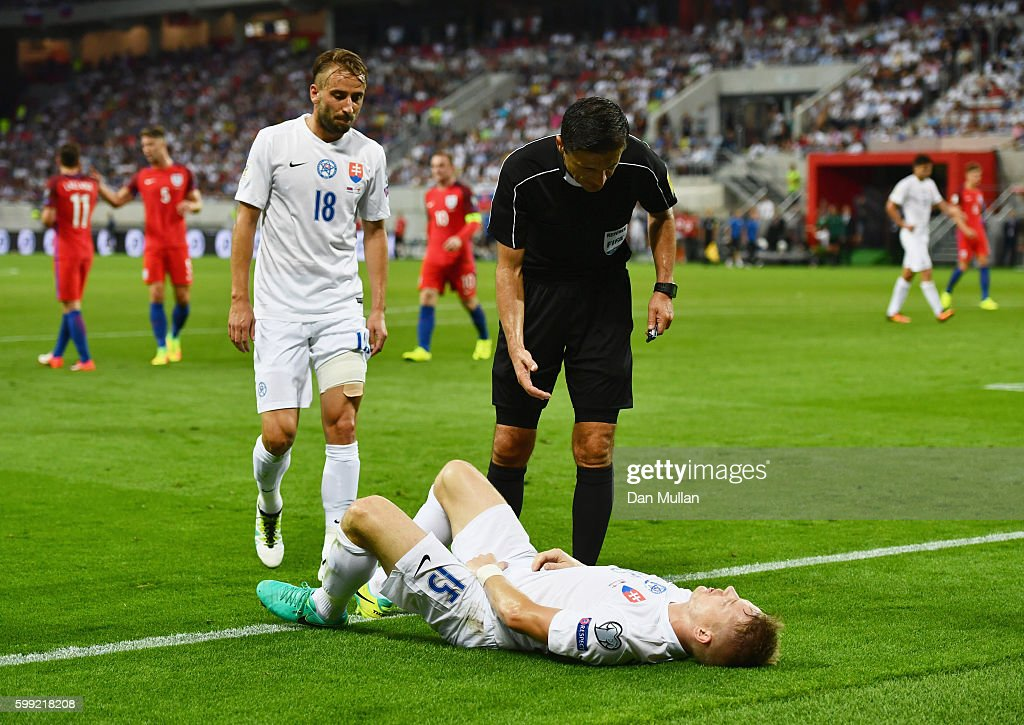 Referee Milorad Mazic stands over Tomas Hubocan of Slovakia as he is injured during the 2018 FIFA World Cup Group F qualifying match between Slovakia and England at City Arena on September 4, 2016 in Trnava, Slovakia.