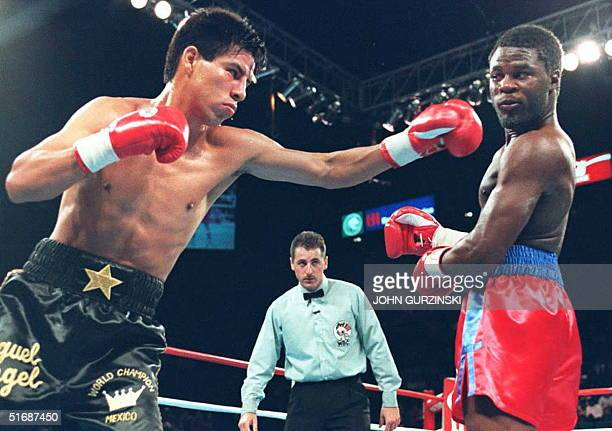 Referee Mitch Halpern looks on as World Boxing Council lightweight champion Miguel Angel Gonzalez of Mexico throws a punch at challenger Lamar Murphy...