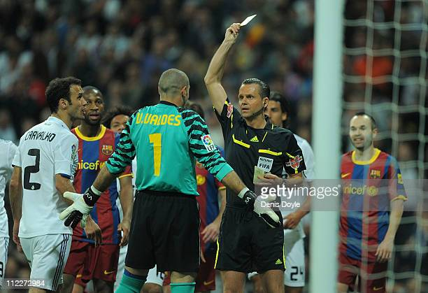 Referee Muniz Fernandez shows the yellow card to Victor Valdes of Barcelona during the La Liga match between Real Madrid and Barcelona at Estadio...