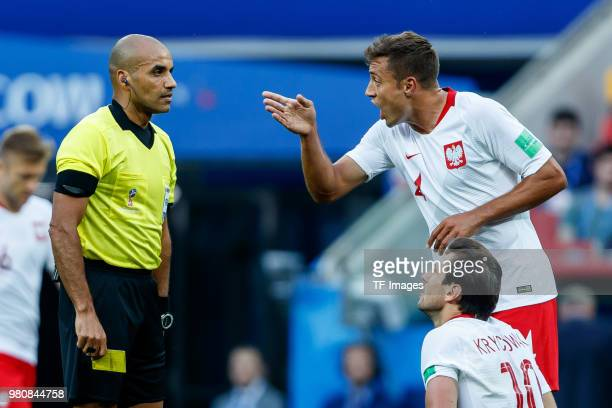 Referee Nawaf Abdulla Shukralla speaks with Thiago Cionek of Poland during the 2018 FIFA World Cup Russia group H match between Poland and Senegal at...