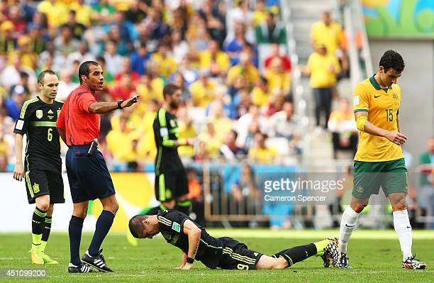 Referee Nawaf Shukralla gestures after a challenge between Fernando Torres of Spain and Mile Jedinak of Australia during the 2014 FIFA World Cup...